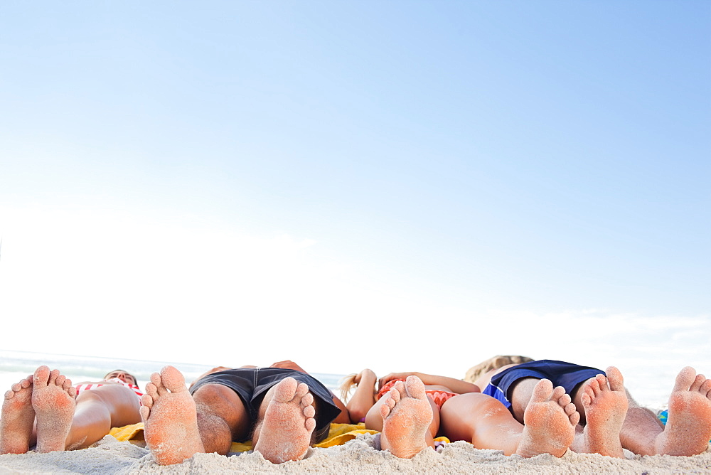Two couples lying on their backs soaking up the sun - 1120-1312