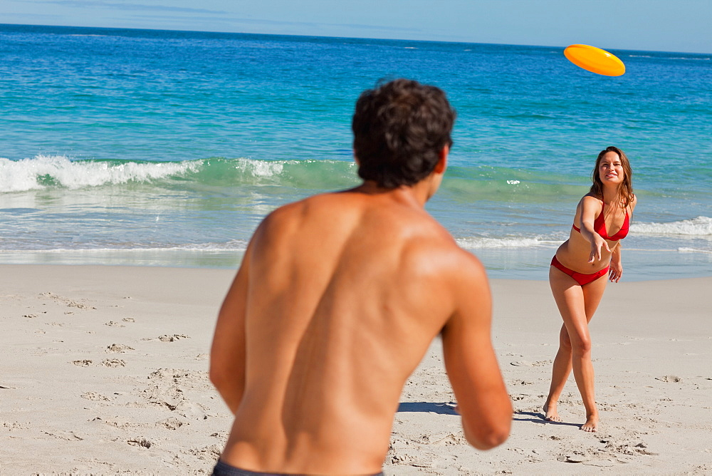 Attractive couple playing with a Frisbee on the beach  - 1120-1429