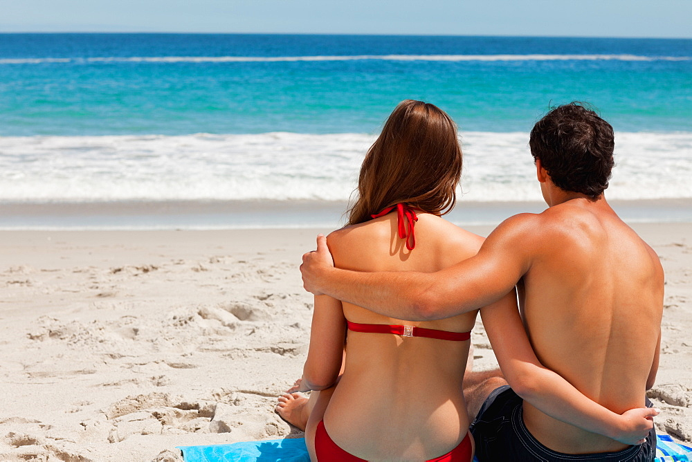 Rear view of a young tanned couple sitting on beach towel  - 1120-1491