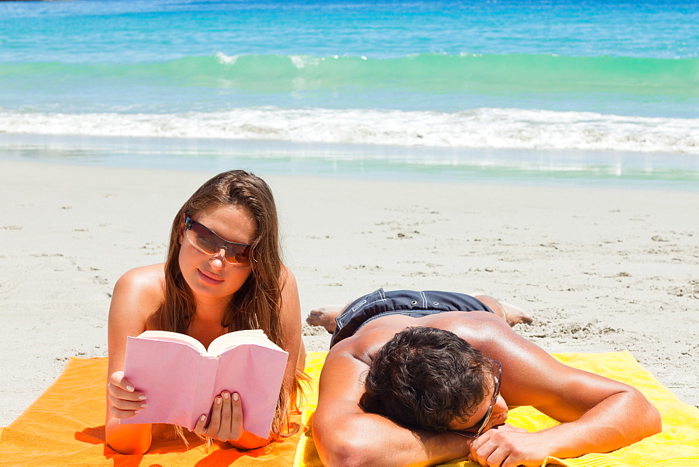 Tanned duo on the beach with the woman reading - 1120-1571