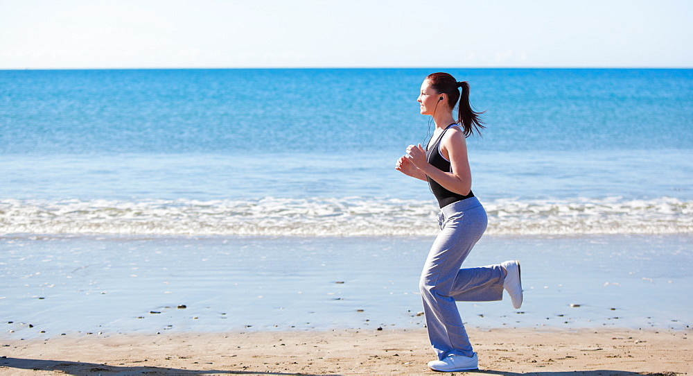Sporty woman running on the beach and listening to music - 1120-2217