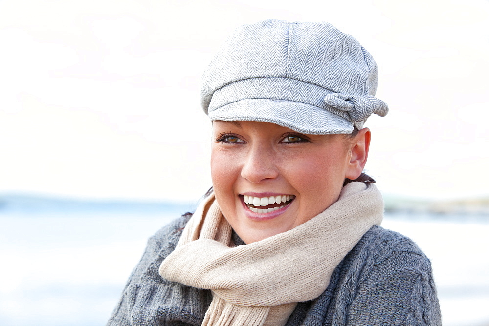 Pretty woman with scarf and hat standing on the beach - 1120-2228
