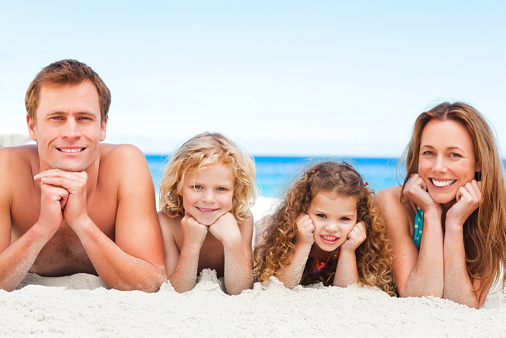 Smiling family lying on the beach - 1120-611