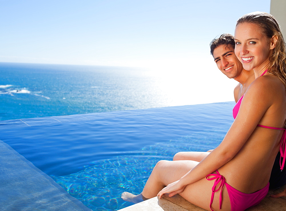 Smiling couple sitting on the pool edge - 1120-674