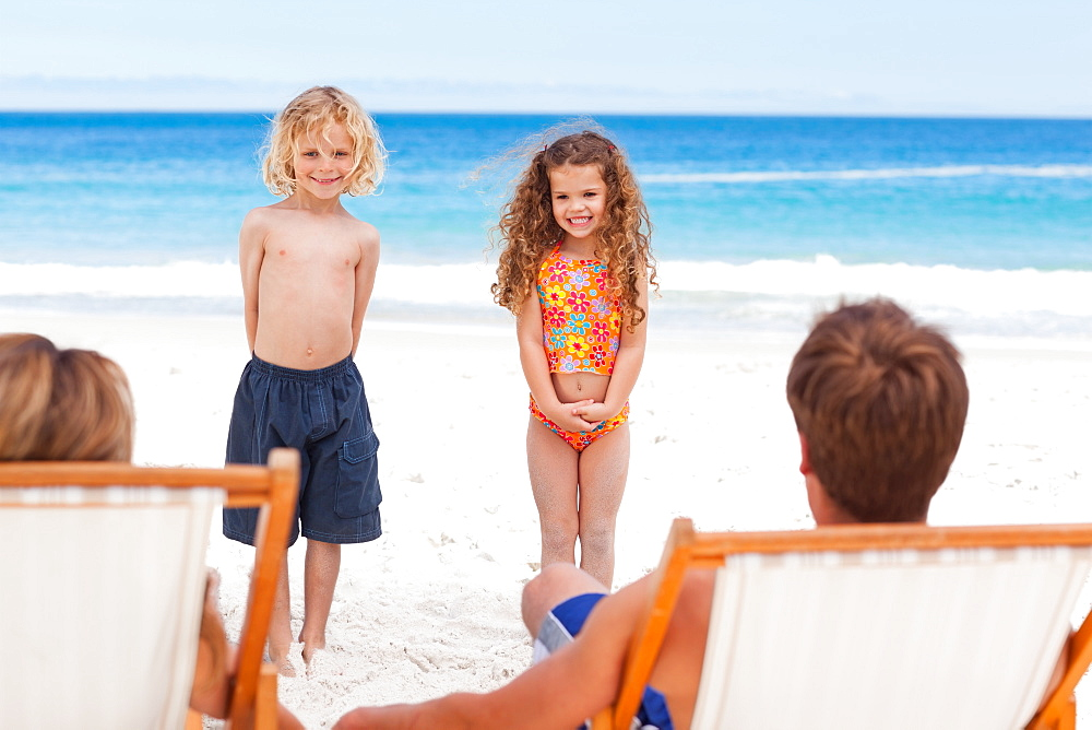 Children standing in front of their parents on the beach - 1120-838