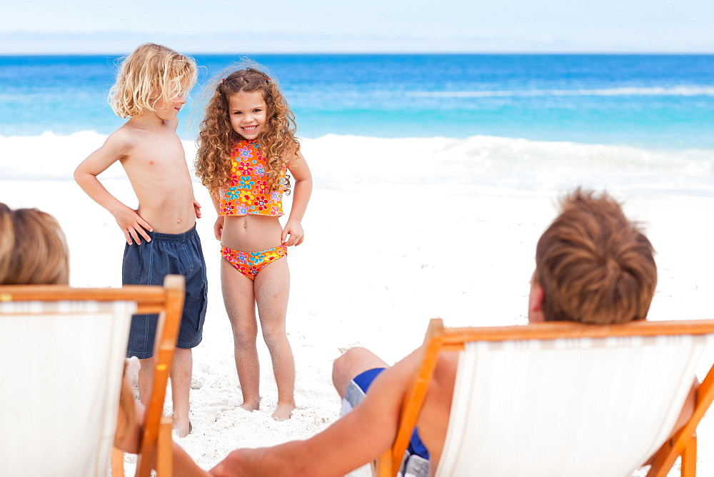 Children on the beach standing in front of their parents - 1120-839