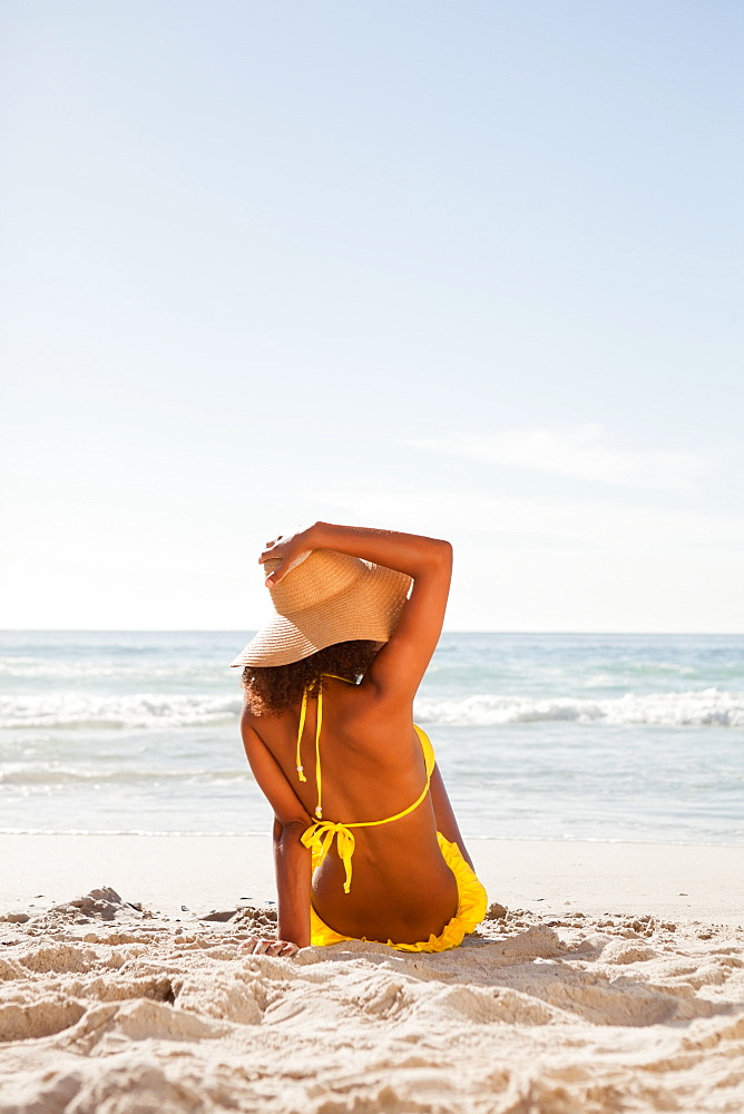 Rear view of an attractive woman holding her hat while looking at the ocean - 1120-1003