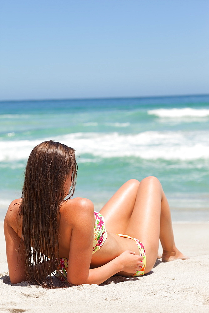 Woman looking towards the sea as she sunbathes on the sand