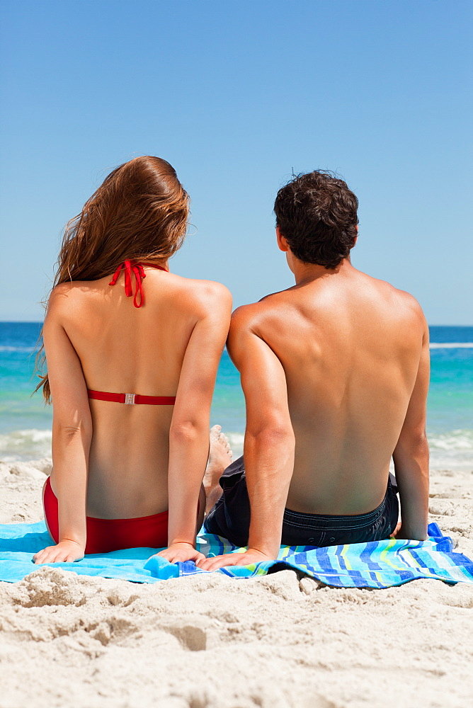 Rear view of a tanned couple sitting on a blue beach towel  - 1120-1499
