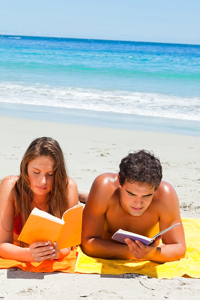 Tanned couple reading a book while lying on the beach  - 1120-1565