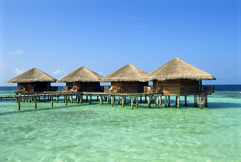 Thatched cabins above the ocean on the tropical island of Baros in the Maldive Islands, Indian Ocean, Asia