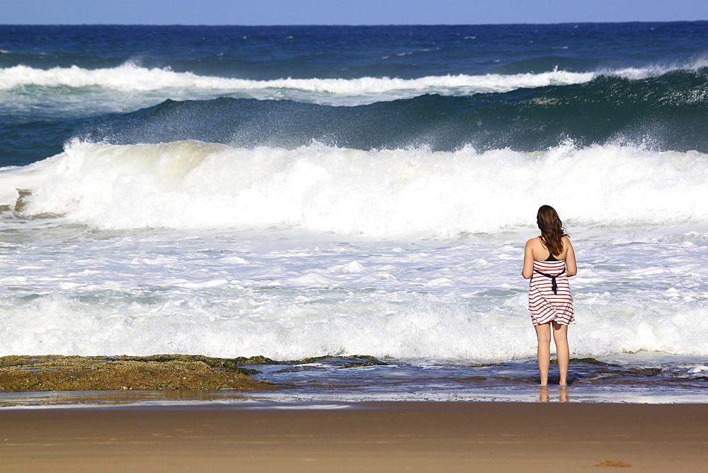 A young woman stands by crashing waves at the beach, St. Lucia Wetlands, Kwa-Zulu Natal, South Africa, Africa
