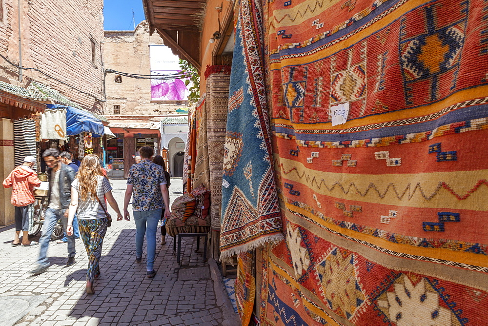 Tourists and locals walking alongside traditional rugs in the Medina's souks, Marrakech, Morocco, North Africa, Africa