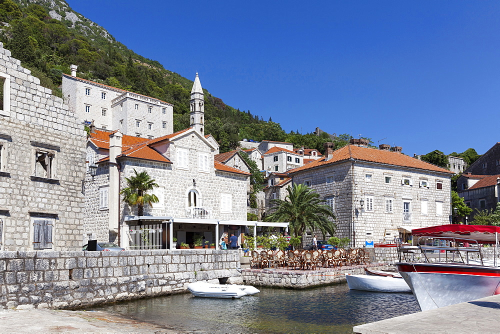Perast harbour with cafes and boats moored up, Bay of Kotor, UNESCO World Heritage Site, Montenegro, Europe