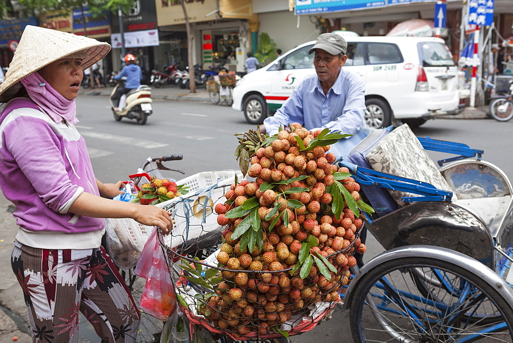 A cycle rickshaw driver stops to buy fruit from a lady outside Ben Thanh Market, Ho Chi Minh, Vietnam, Indochina, Southeast Asia, Asia