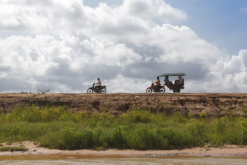 A motorbike being followed by a moto-rickshaw along the banks of the Tonle Sap Lake, Cambodia, Indochina, Southeast Asia, Asia