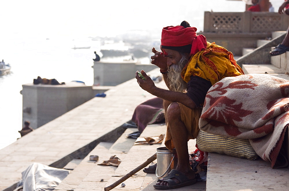 A Saddhu applies a tikka to his forehead while sitting at a ghat on the banks of the River Ganges, Varanasi, India - 1005-113