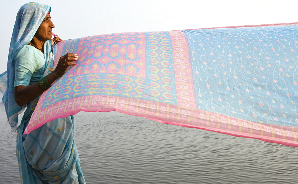 A woman drys a sari on the banks of the river Ganges, Varanasi, India. The river is at the centre of all the peoples activities from the spiritual to the mundane. - 1005-117