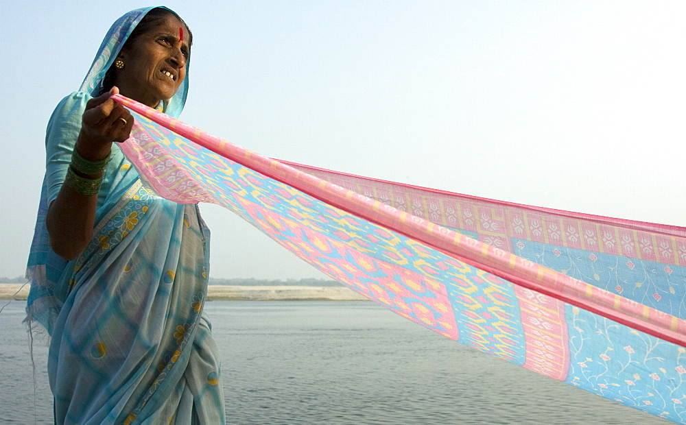 A woman drys a sari on the banks of the river Ganges, Varanasi, India. The river is at the centre of all the peoples activities from the spiritual to the mundane. - 1005-118