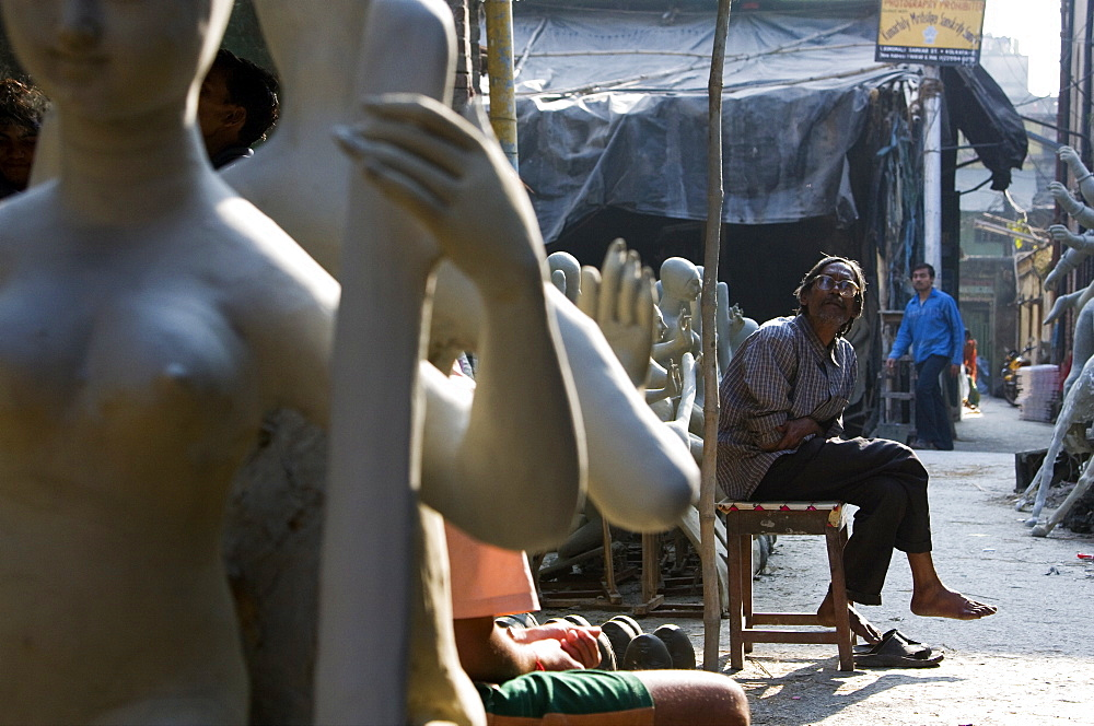 A local artisan sits amongst partially finished statues of indian idols in Calcutta, India