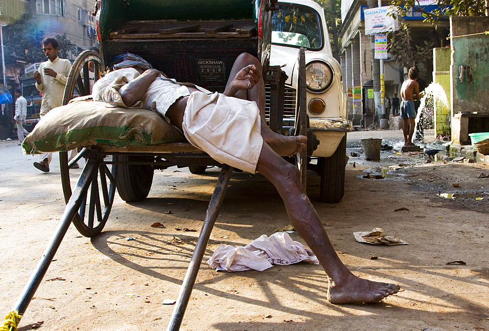 A tired rickshaw wallah takes a break from a long day pulling his passenger rickshaw around the busy streets of Calcutta, India. - 1005-127