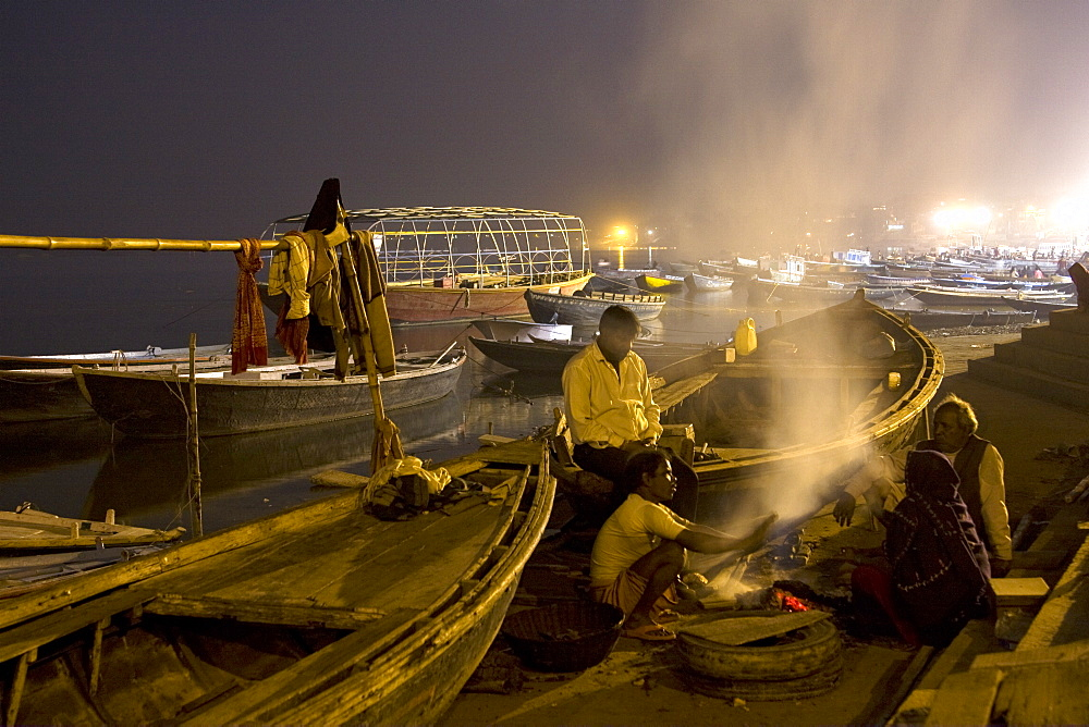 Surrounded by boats, men socialize around a fire on a ghat in the ancient city of Varanasi, India. - 1005-144