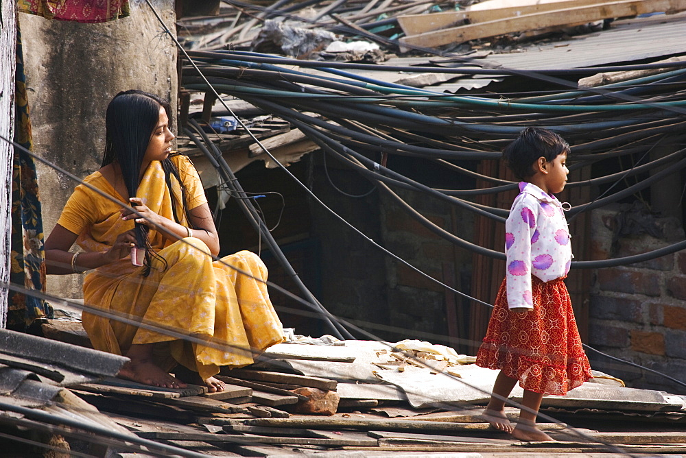 A woman combs her hair while sitting in amongst the many power cables feeding a Kolkata slum, India - 1005-153