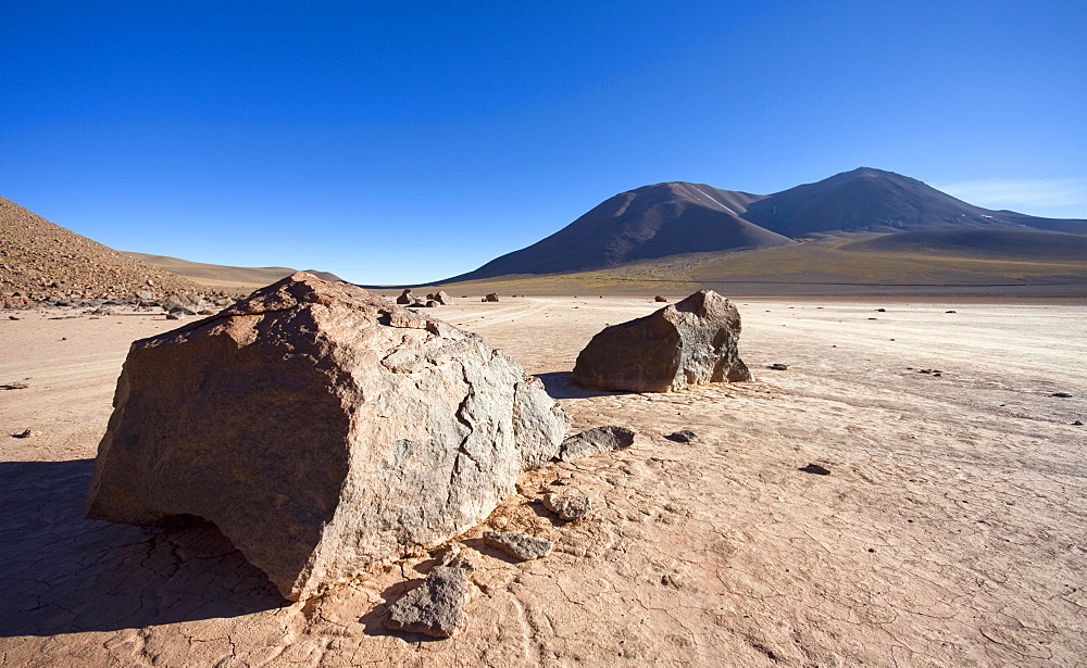 A volcanic rock sitting high up in the Atacama Desert, Chile. The volcano Corona is in the background. - 1005-3