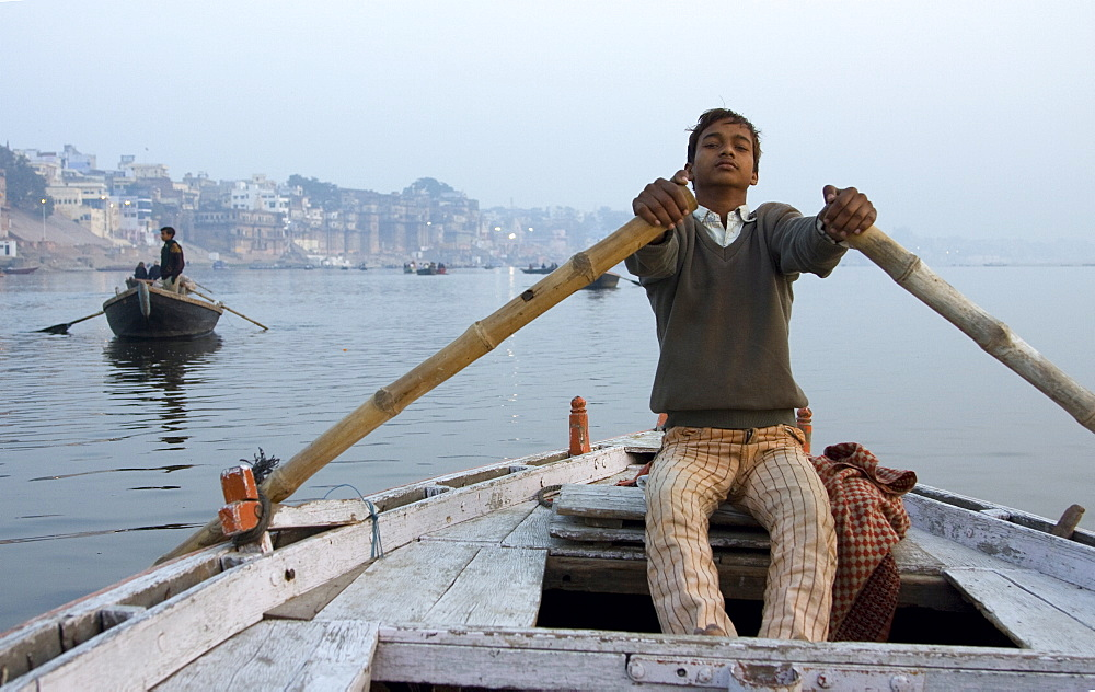A boy rows a boat on the Ganges, India's most sacred river. Varanasi, India. - 1005-43