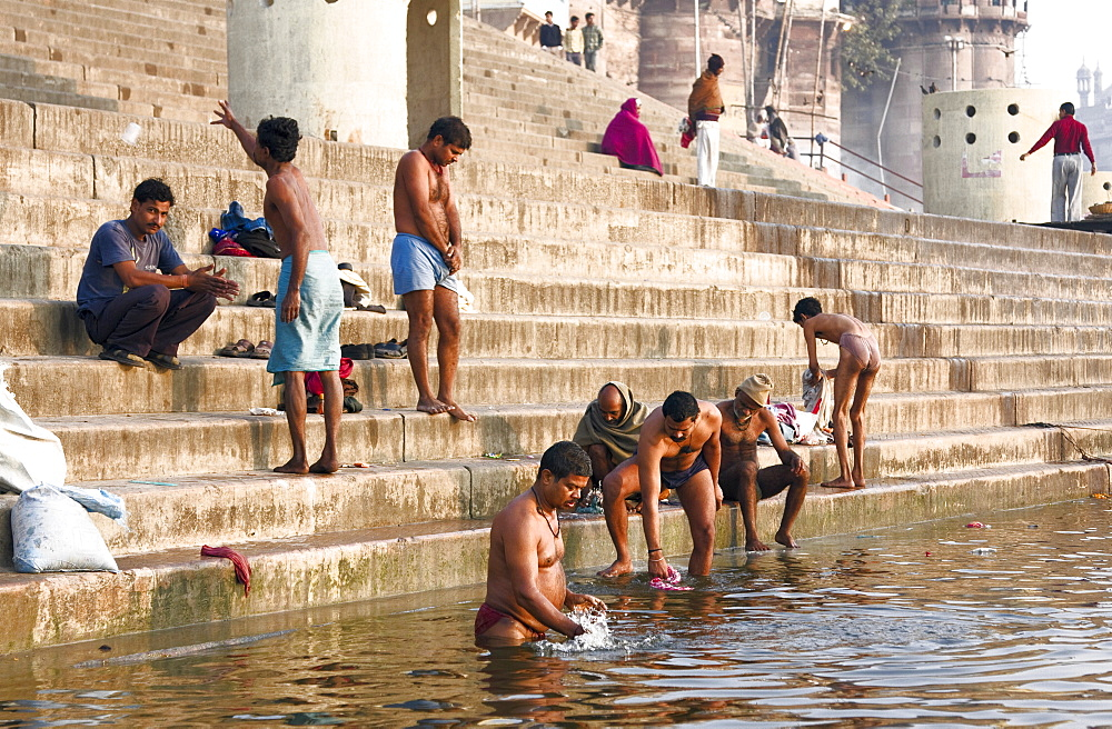 Hindu pilgrims and local people wash and worship in the river ganges at a Varanasi ghat, India. - 1005-6