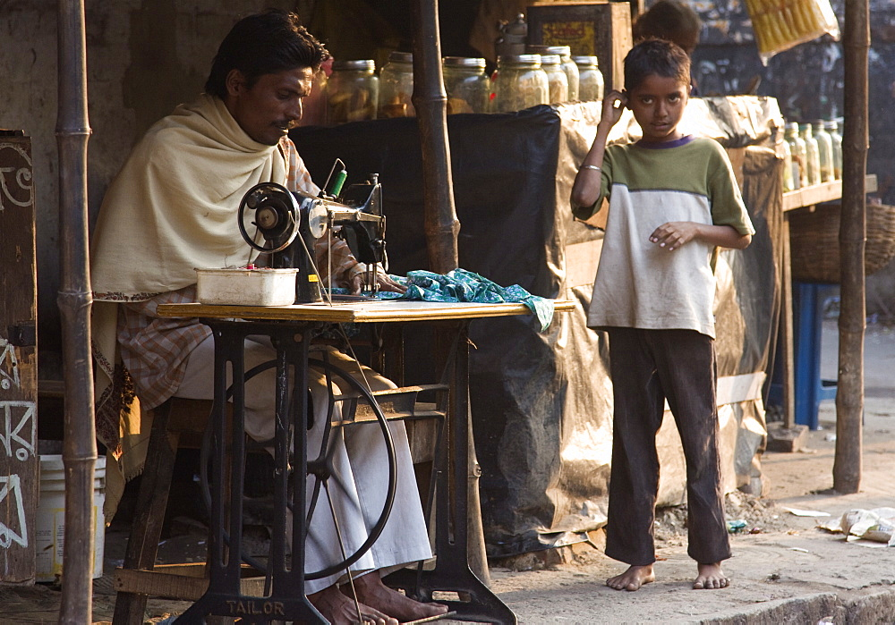 A tailor mends an article of clothing while a young boy looks on. Kali Ghat, Calcutta, India. - 1005-73
