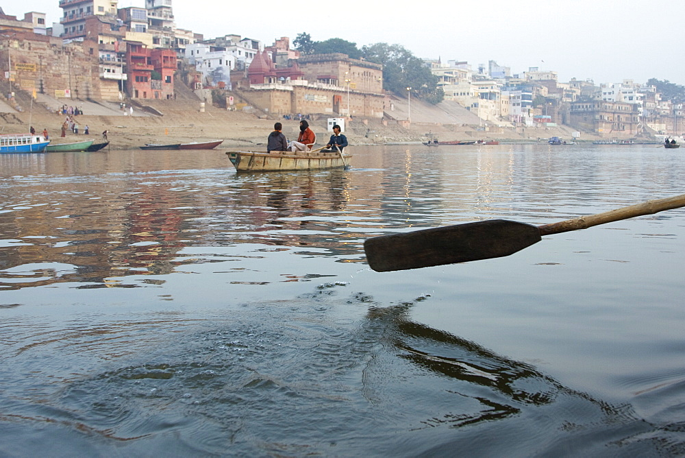 Detail of an oar as it leaves the water, while rowing along the Ganges, the most sacred river in India. The bathing ghats of Varanasi in the background. - 1005-89