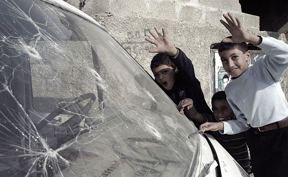 Palestinian children standing next to a car riddled with bulletholes, Nablus, West Bank, Palestine.