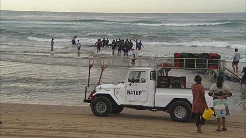 Sardine Run, people pulling net through surf, wide shot, South Africa