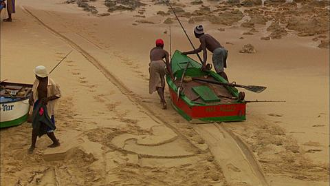 People, fishermen, two men push red, green boat into water, row out, Tele, Mozambique