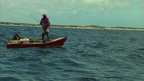 People, fishermen, man standing on boat, rough seas fishing with pole, two, Mozambique
