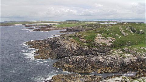 Aerial, Coll, Scotland, Tiree, over rocky fields with black goat herd, Scotland, UK