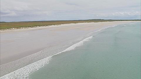 Aerial, Coll, Scotland, along surf line of Hynish Bay, Tiree, Scotland, UK