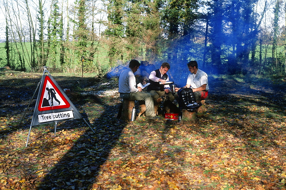 Tree surgeons resting by the fire, UK