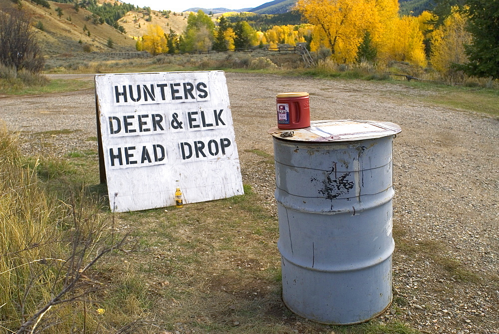 'Hunters Deer and Elk head drop' sign and barrel, Wyoming, USA. The Wyoming Game and Fish Department collect samples from deer and elk during the hunting season to test for Chronic Wasting Disease (CWD) in the state's deer and elk herds.  Chronic wasting disease is a fatal neurological disease that has been diagnosed in free ranging deer, elk and moose in 11 states and two Canadian provinces.