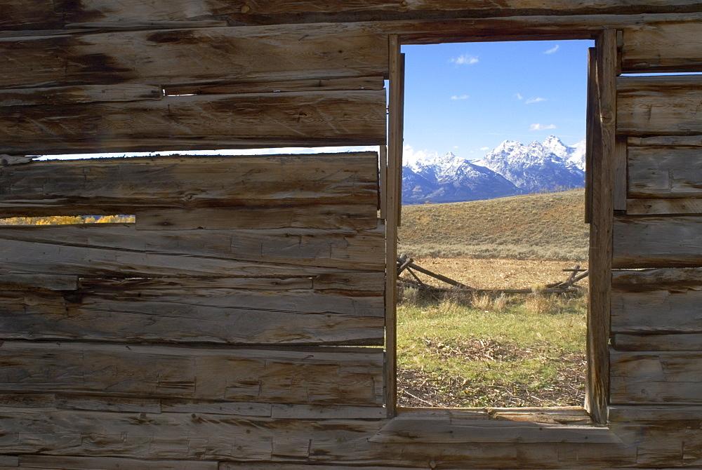 Looking through window of abandoned barn at Teton Mountain range, Wyoming, USA