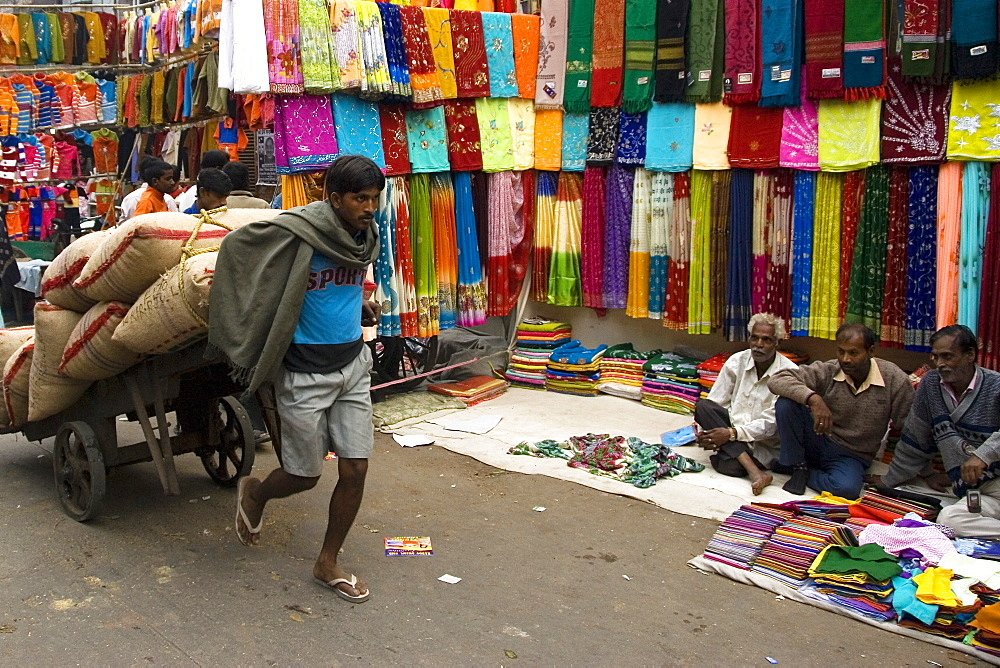 Man pulling cotton sacks on cart in Chandni Chowk shopping district of New Delhi, India