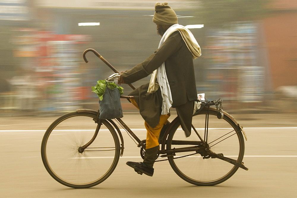 Elderly man carrying shopping on bicycle, Agra, Uttar Pradesh, India