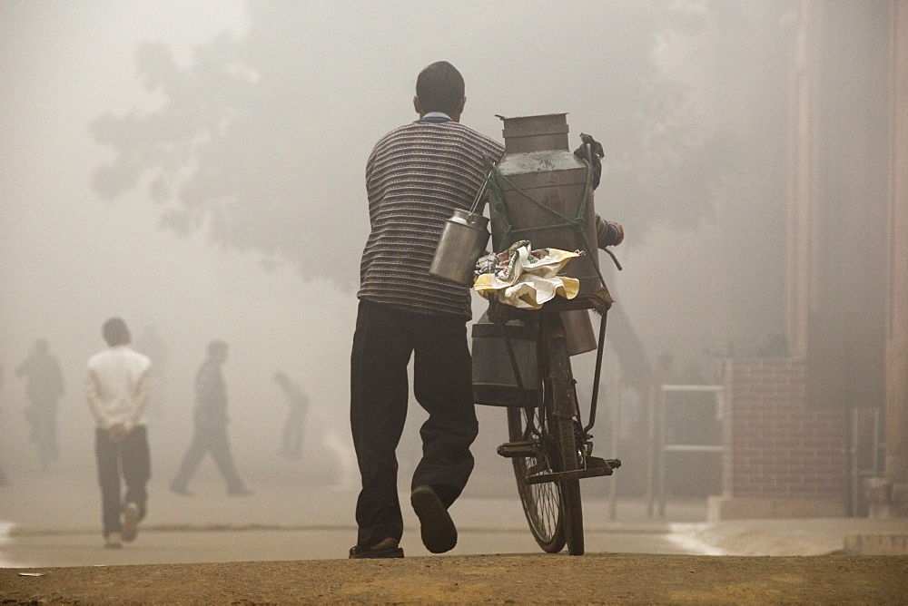 Man pushing bicycle loaded with equipment through early morning mist and atmosphere, Agra, Uttar Pradesh, India - 1024-305