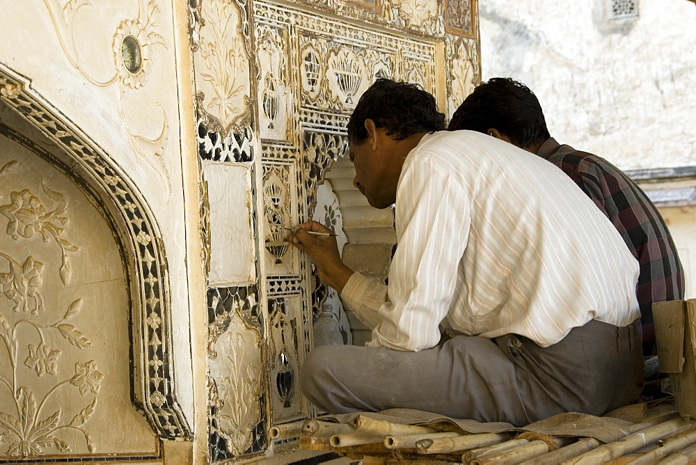 Artisans carrying out repairs on the plasterwork relief at the Amber Fort, Rajasthan, India