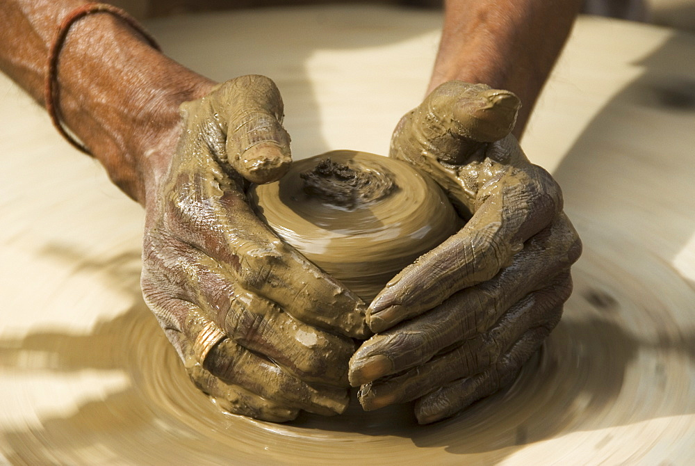Potter creating clay pots on a manual stone wheel, Udaipur, Rajasthan, India