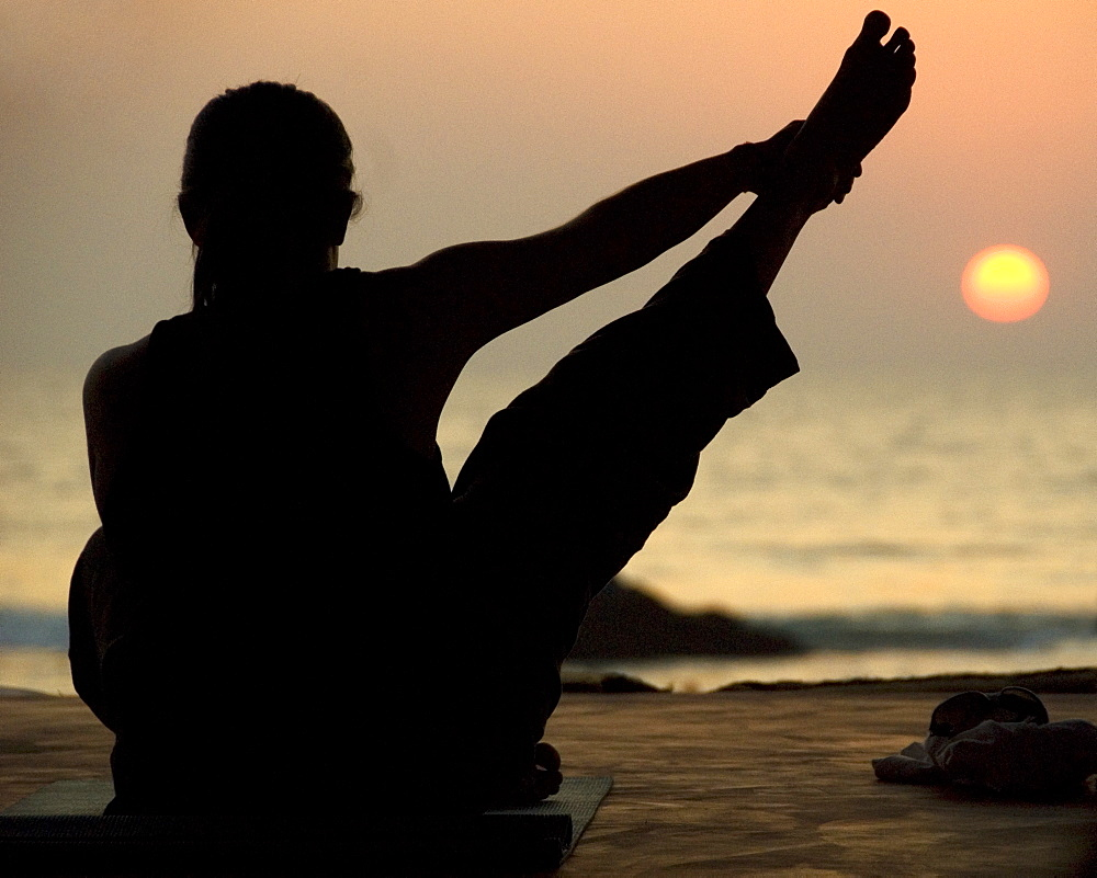 Young woman practicing Yoga at sunset on the beach, Goa, India - 1024-343