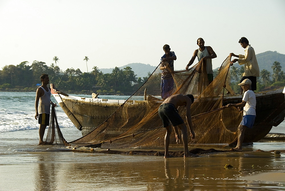 Fishermen untangling fishing nets on the beach after hauling in a catch, Goa, India