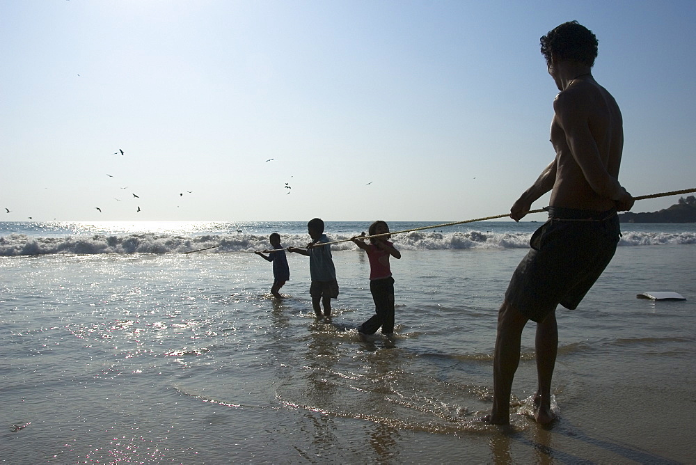 Man and three children hauling in the fishing net on the beach, Goa, India