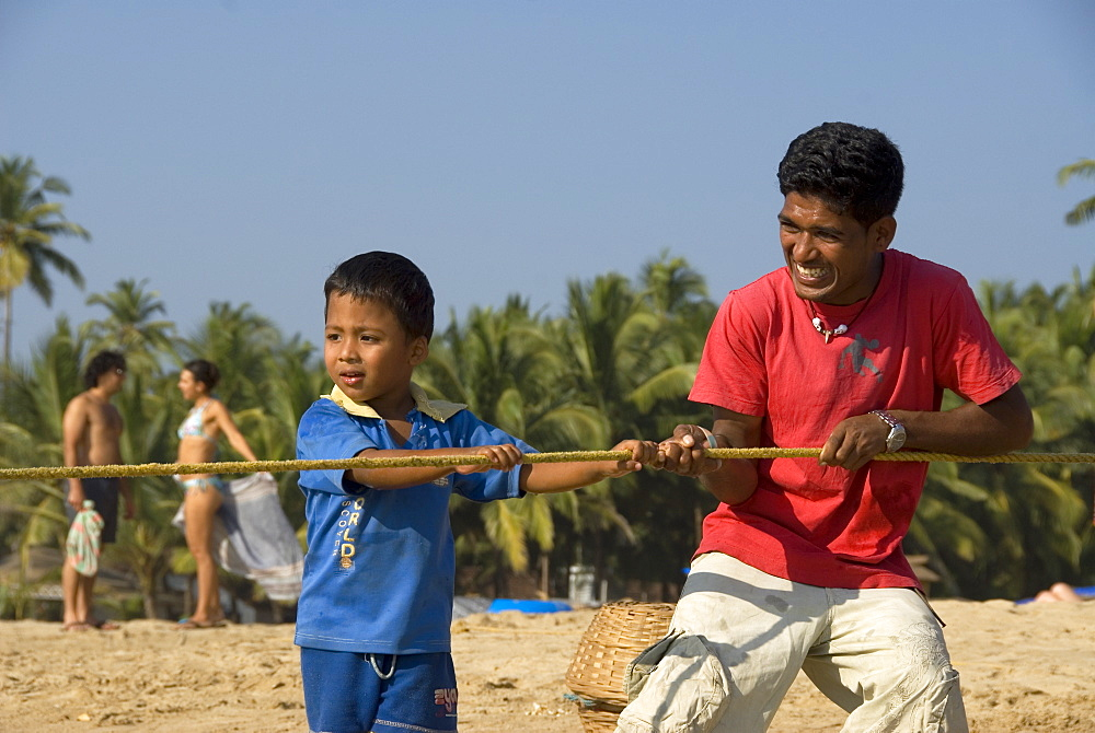 Man and boy hauling in fishing net from the beach, Goa, India